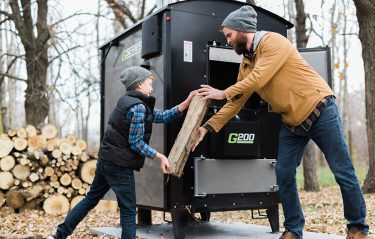 Dad and son loading their outdoor wood furnace
