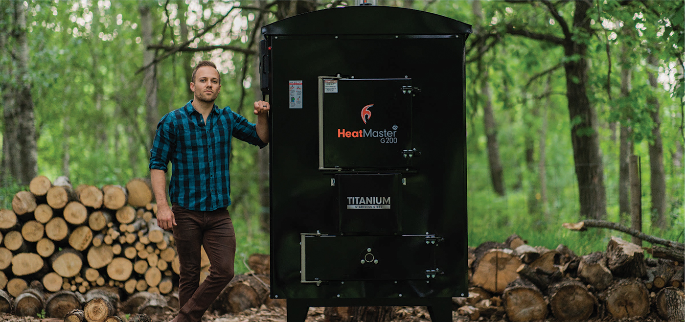 Man standing beside his G200 outdoor furnace from HeatMasterss