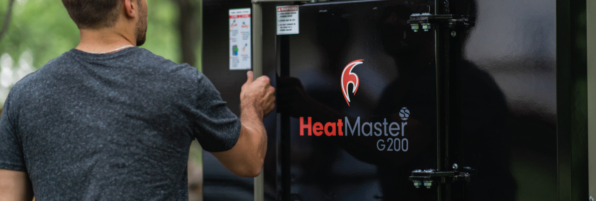 Man opening his HeatMaster outdoor wood boiler