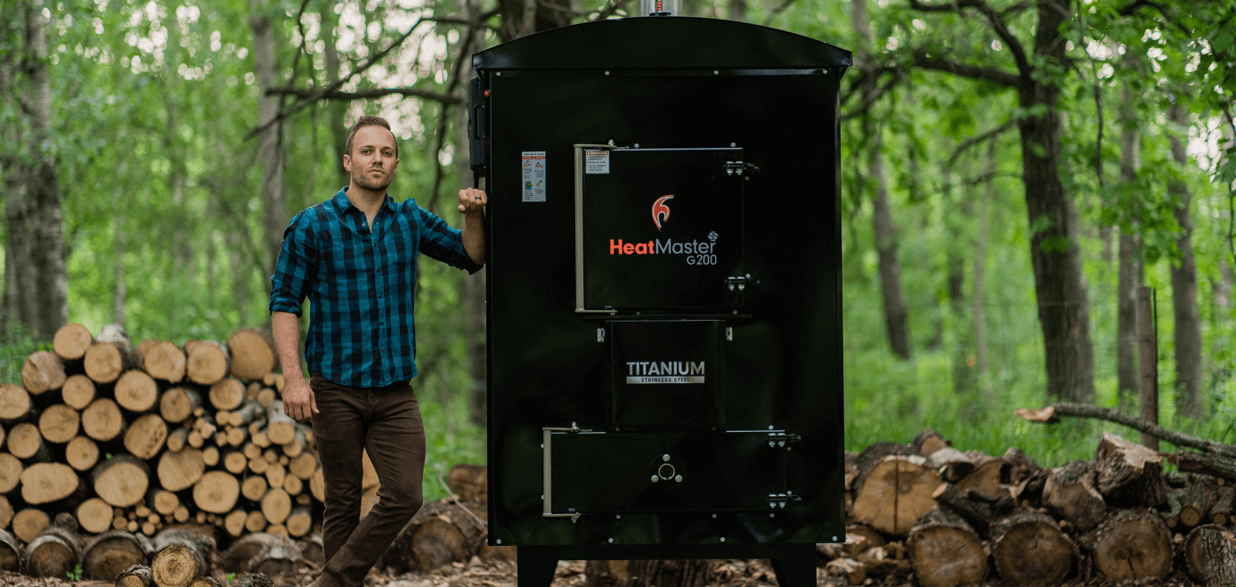 Man standing beside his HeatMaster outdoor wood boiler